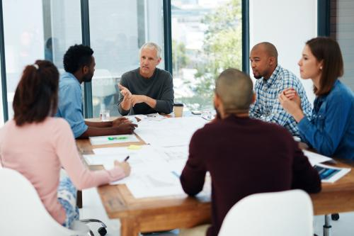 image of seceral diverse people sitting around a meeting table