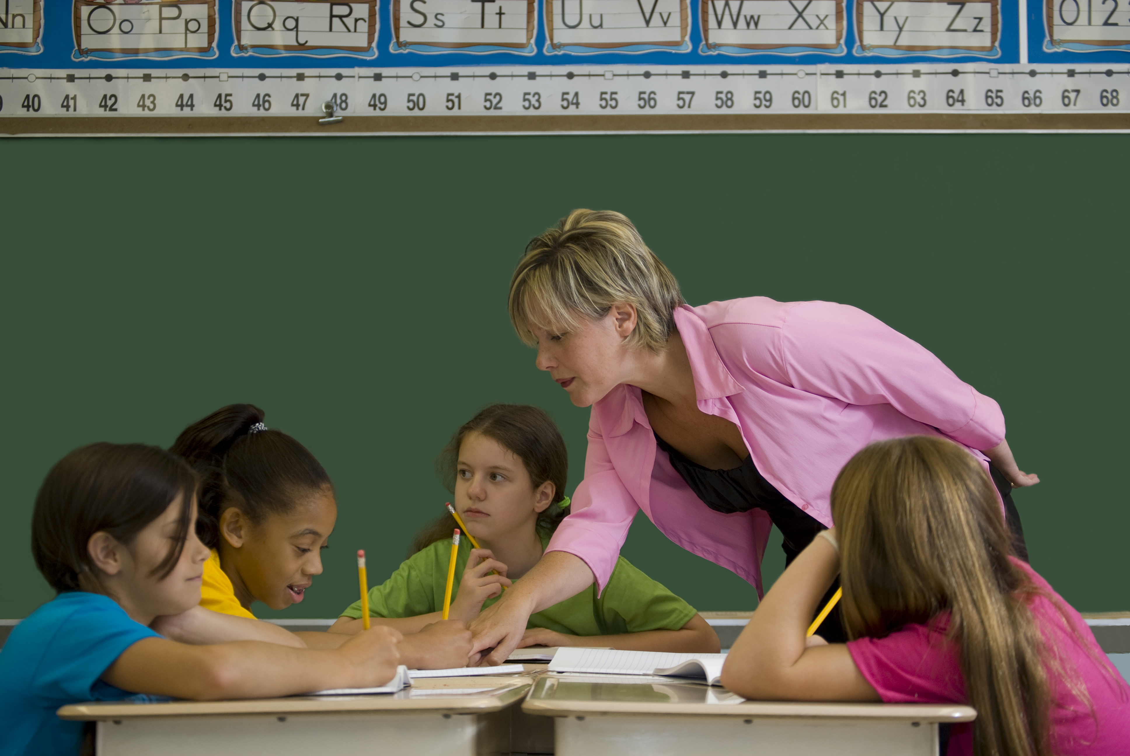 a photo of a teacher leaning over a group of young students