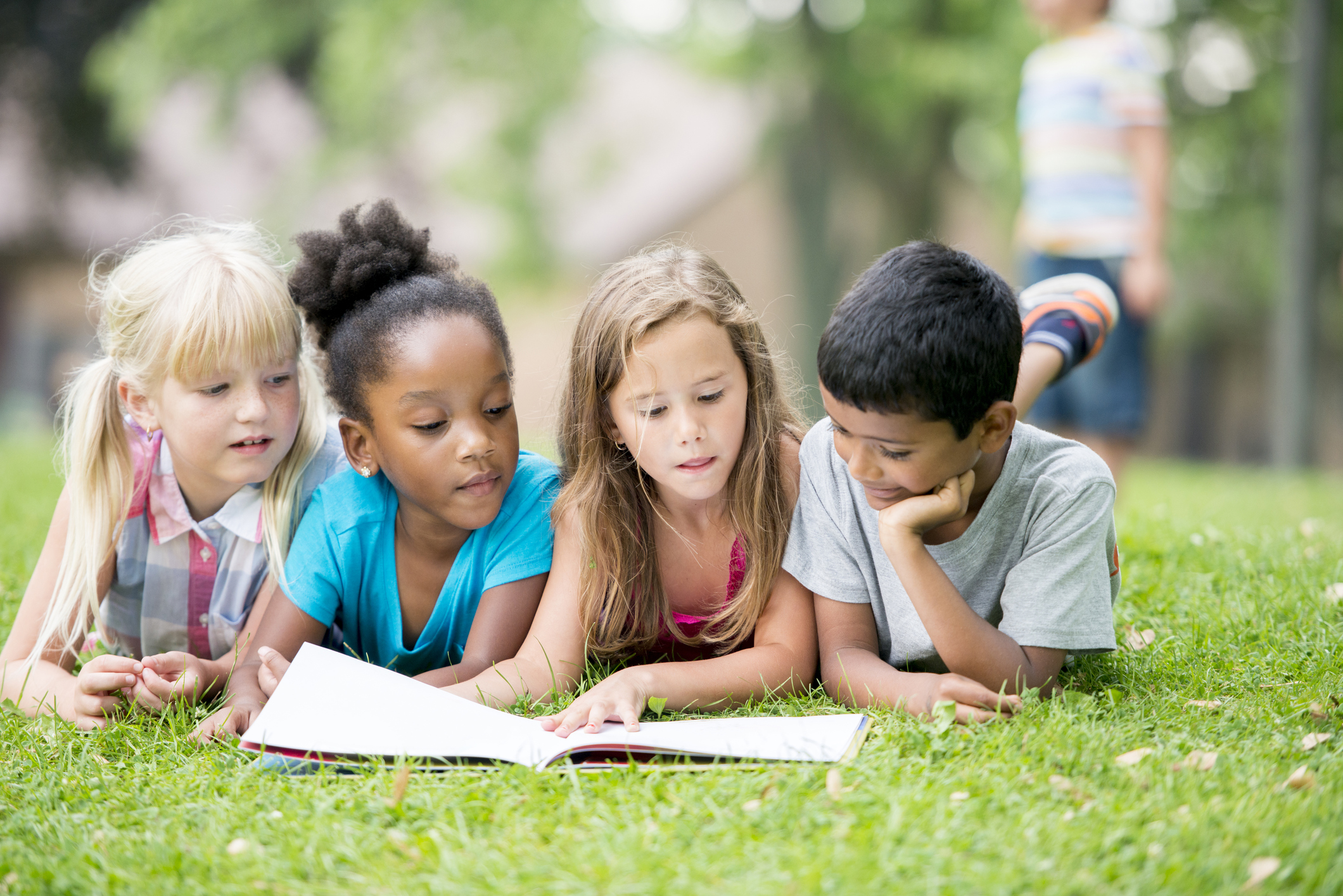 photo of 4 kids laying on grass looking at an open book